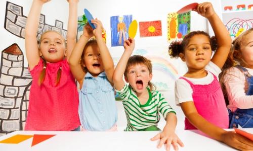 Groupe de 5 enfants s'amusant, avec des dessins en arrière-plan, ils lèvent les mains au ciel et crient