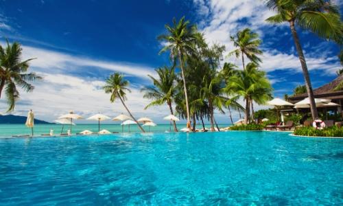 Paysage des Caraïbes, eau turquoise, palmiers, parasols blancs