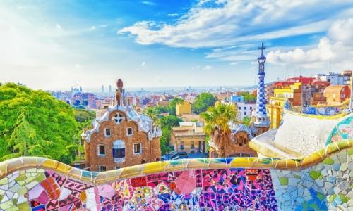 Vue sur le Parc Güell à Barcelone avec beaucoup de couleurs vives, arbres, bâtiments