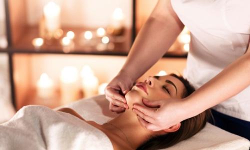 Femme se faisant masser le visage au spa, bougies en arrière-plan