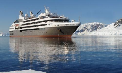 bateau de croisière ponant sur l'eau entouré de glacier