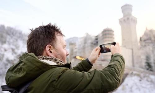 Homme de profil entrain de prendre une photo avec son téléphone