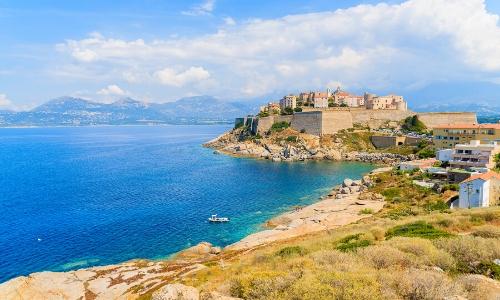 Vue sur le bord de mer de la Corse, avec les montagnes en arrière-plan
