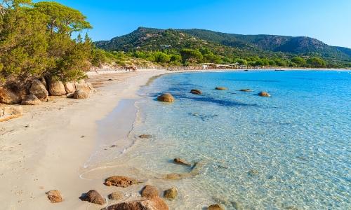Plage tranquille en Corse, avec sable, et nature, eau cristalline, rochers