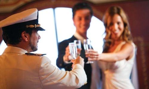 Un membre de l'équipage de Costa Croisières porte un toast avec des passagers