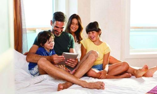 membres d'une famille qui sont assis sur le lit d'une cabine de bateau