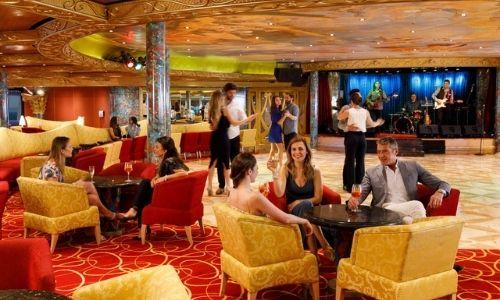 espace de luxe rouge et or d'n bateau avec des personnes qui discutent dans des canapés