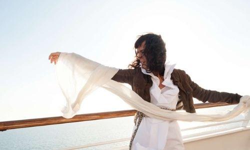 jeune femme sur le pont d'un bateau, portant un voile qui vole au vent