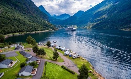 Vue depuis un fjord norvégien avec montagnes, lac, verdure, bateaux de croisière au loin