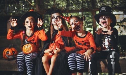 Groupe d'enfants assis côte à côte en déguisements d'halloween