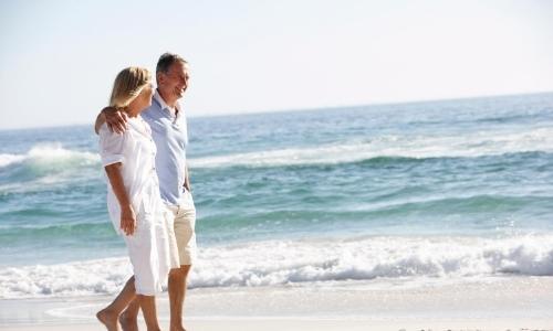 Couple marchant sur la plage, souriant