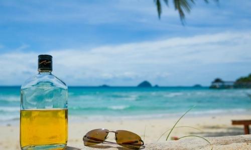 Bouteille de rhum sur une plage de sable blanc, avec lunettes de soleil