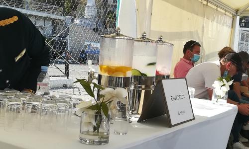 Barman proposant des jus detox aux passagers patientant avant l'embarquement sur le Lyrial