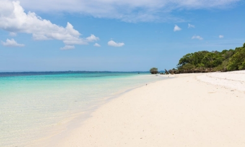 Plage de sable blanc avec eau turquoise, ambiance paradisiaque