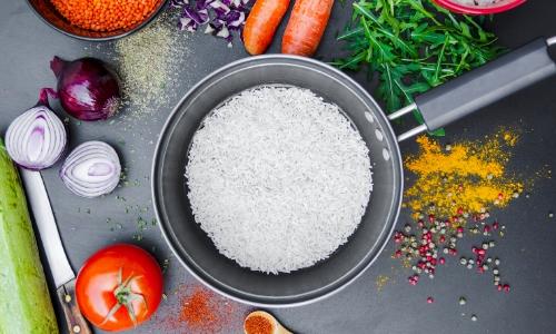Photo d'un plat pour faire cuire le riz, des oignons coupés, des carottes, une tomate, de la salade et un couteau