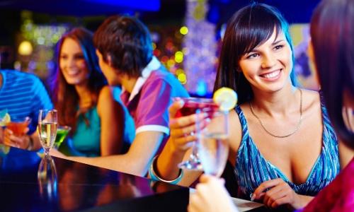 Des personnes dans un bar entrain de faire connaissance, tenant des cocktails à la main