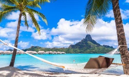 hamac au premier plan accroché à des palmiers sur le sable avec la mer turquoise en paysage et des montagnes au loin