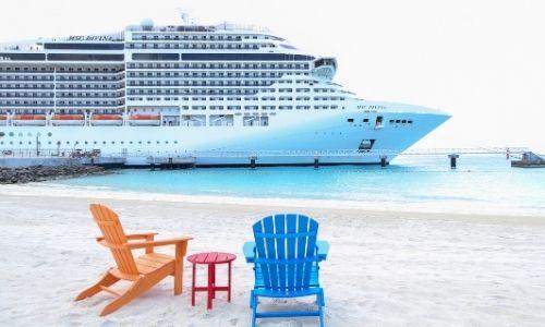 une chaise en bois peinte en orange et une autre en bleue, accompagnées d'une petite table rouge sur le sable avec un bateau MSC sur l'eau en arrière-plan.