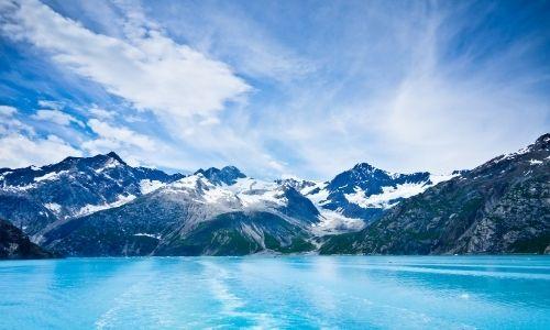 paysages de montagnes, légèrement enneigées avec la mer d'un bleu clair vif au premier plan