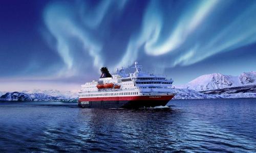 Une aurore boréale lors du passage d'un bateau Hurtigruten