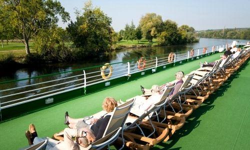 Rangée de passagers qui profitent du soleil sur les transats d'un pont d'un bateau fluvial