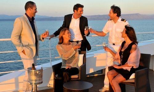 Membre de l'équipage qui boit un verre avec des passagers du bateau