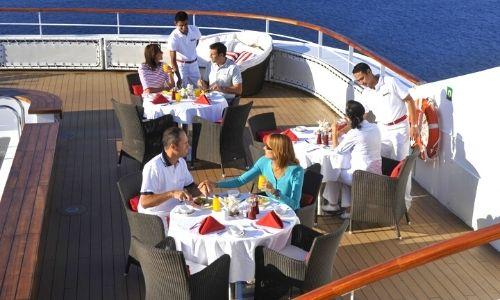 Passagers qui sont à table sur la terrasse du bateau, la table est dressée