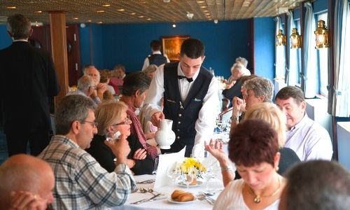 Passagers qui sont à table dans un restaurant du bateau