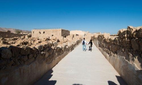 couple qui marche main dans la main dans une ruelle en Arabie Saoudite en pleine journée