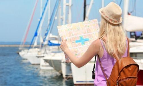 jeune femme de dos qui regarde une carte face à la mer et aux bateaux