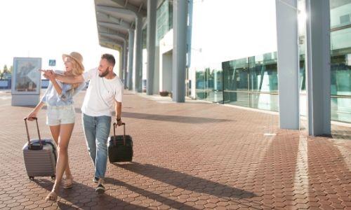 un couple en dehors de l'aéroport, roulent des valises et indiquent avec leurs mains entrelacées une direction