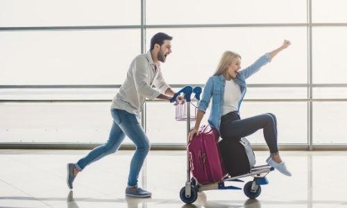 un jeune homme pousse une jeune femme assise sur un porte valise dans un aéroport avec enthousiasme