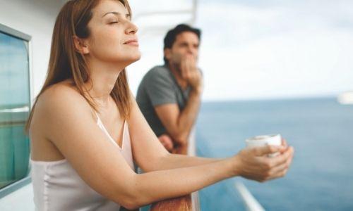 jeune femme qui respire le grand air sur le balcon d'une croisière et jeune homme en arrière-plan qui observe la mer, tous deux, adossé à la barre
