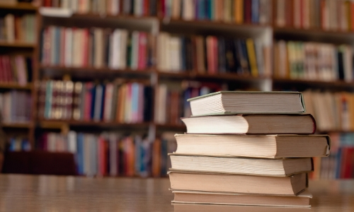 Livres empilés sur une table au premier plan et bibliothèque au fond