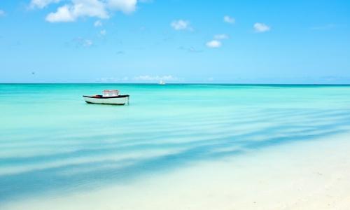 Vue sur les eaux limpides des Caraïbes, avec barque sur l'eau