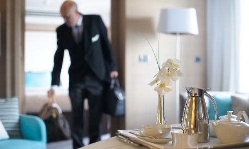 Membre du personnel déposant les affaires de clients dans leur cabine, ambiance luxe, aux petits soins