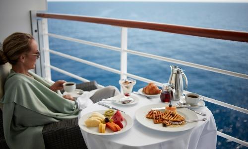 Une femme assise sur sa terrasse de cabine face à la mer, prenant son petit-déjeuner