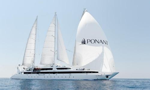 Vue sur un grand voilier de Ponant, blanc, avec inscrit PONANT en noir sur une voile