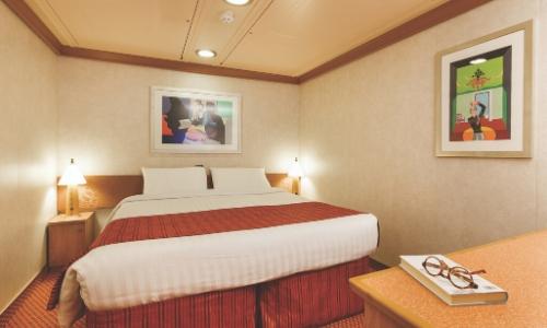 Cabine intérieure avec grand lit, lampes de chevet, table