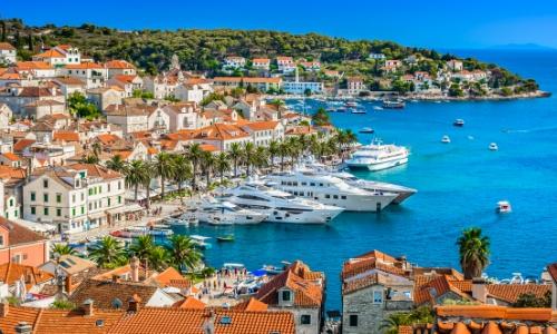 Paysage bord de mer de la Méditerranée avec port, habitations colorées, eau turquoise