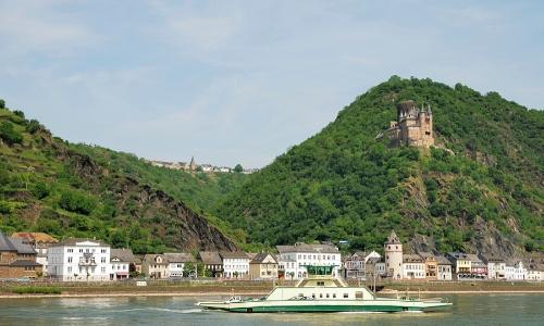 Bateau naviguant tranquillement sur le Rhin, avec petites habitations aux alentours et verdure