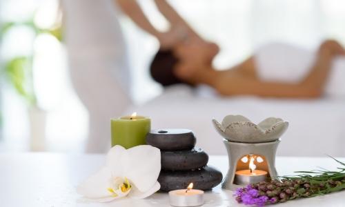 Ambiance spa avec bougies, pierres, fleurs et femme se faisant masser en arrière-plan