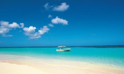 Plage de sable blanc avec eau limpide, ciel bleu et petit bateau