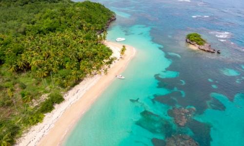 Vue aérienne sur une plage des Caraïbes avec sable blanc, eau turquoise et végétation