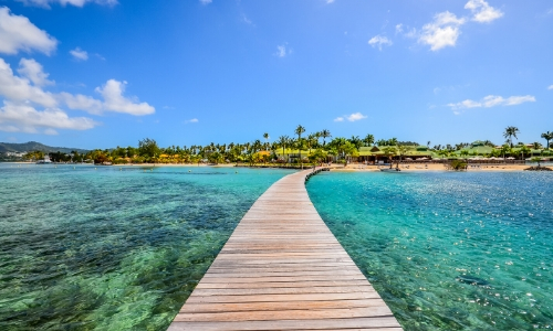 Vue sur un ponton donnant sur la plage en Martinique avec eau turquoise