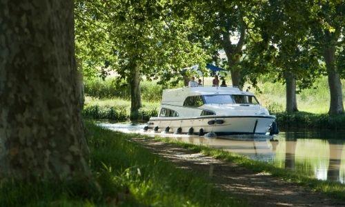 péniche sur un canal français en plein milieu de la nature, des arbres et de verdure