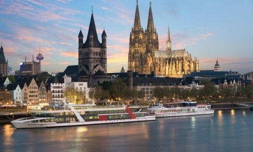 croisière fluviale sur un fleuve au bord d'une ville avec de grands bâtiment dont un clocher illuminé