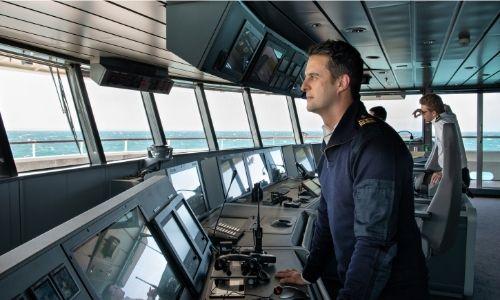commandant qui pilote le bateau de croisière, regardant à l'horizon dans la salle des contrôles