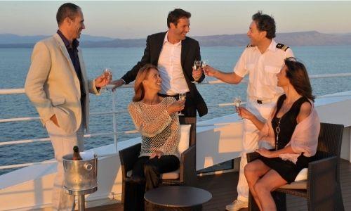 deux couples d'amis qui sont en train de boire un verre et de discuter avec un membre de l'équipage en uniforme sur un bateau