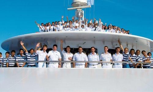 membres de l'équipage qui font des signes de la main, tout sourire en regardant la photo sur le pont supérieur d'un bateau